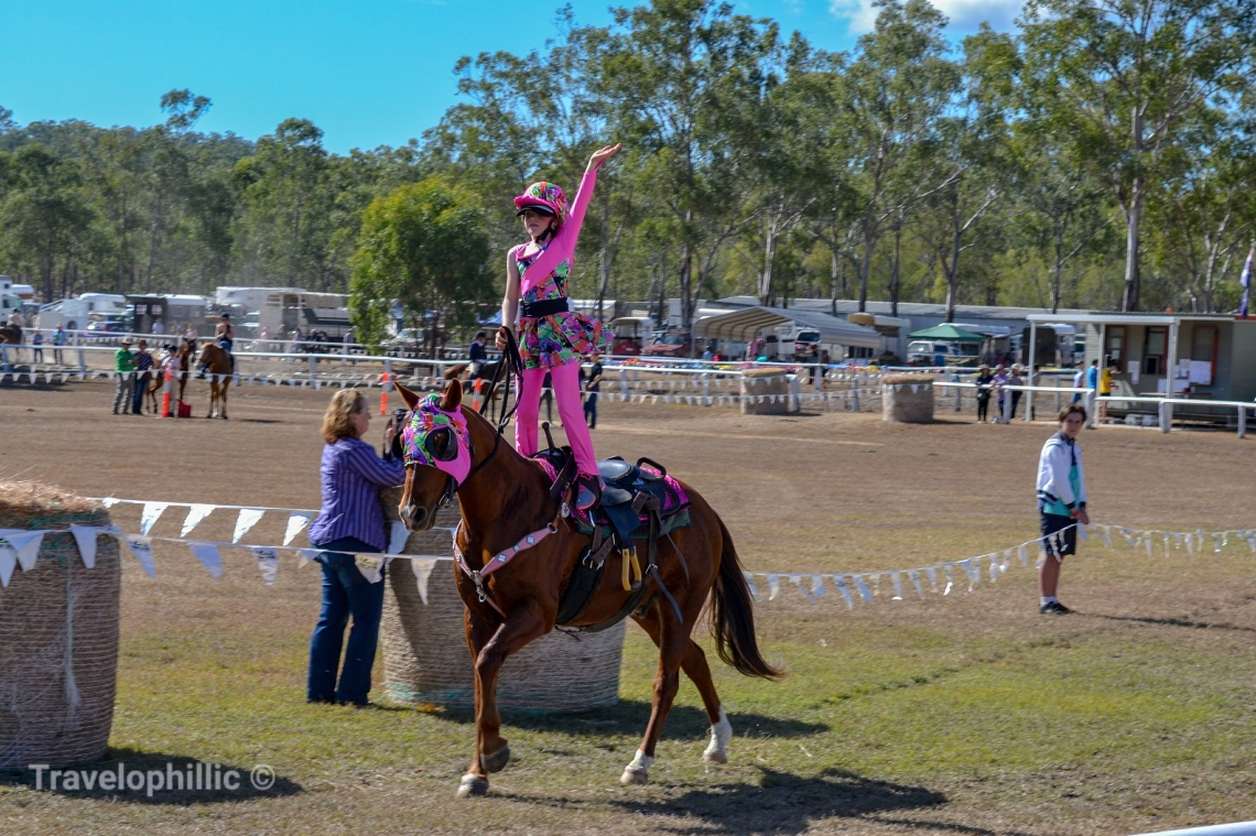 Young rider standing on saddle