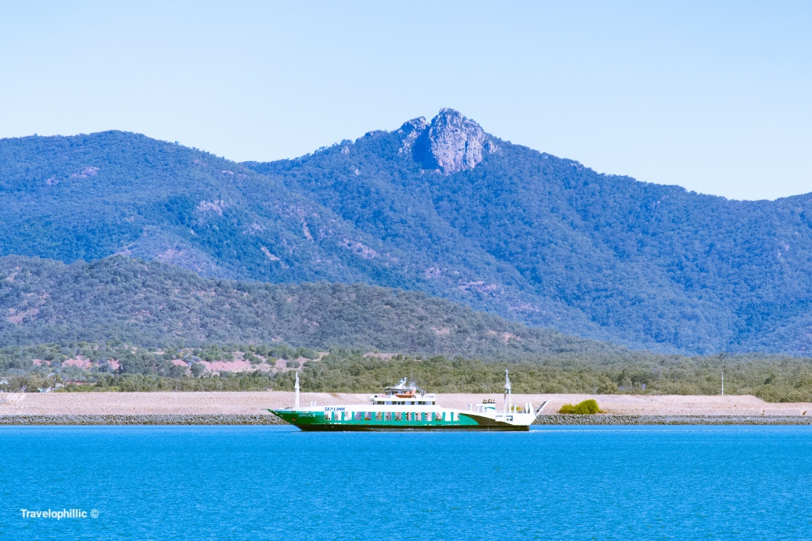 A ship sailing in Gladstone Harbour against a background of Mount Larcom